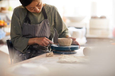 Serious concentrated young Asian woman in apron sitting at table and using cutter while making bowl in workshop