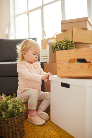 Curious girl opening moving box