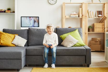 Adolescent boy choosing music on smartphone