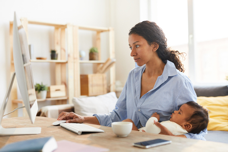 Conceptrice de mère travaillant sur le projet tout en allaitant bébé