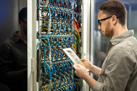 Data center technician checking connections on tablet Stock Photo