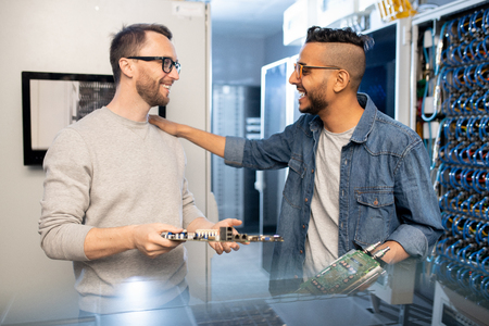 Excited engineers repairing motherboards in server room Stock Photo