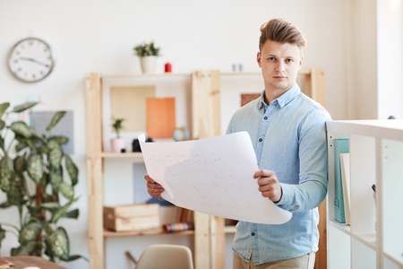 Young architect analyzing blueprint