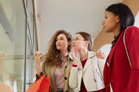 Girls choosing dress in shopping display