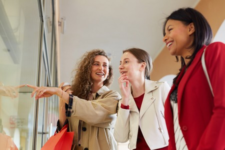Happy friends discussing fashion in mall Фото со стока