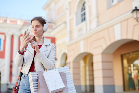 Modern girl in headphones walking after shopping
