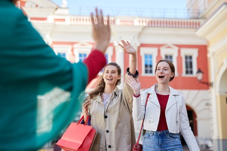Excited friends meeting on street