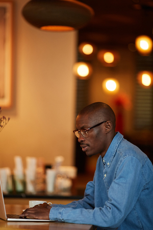 African Man Working with Laptop in Cafe Stock Photo