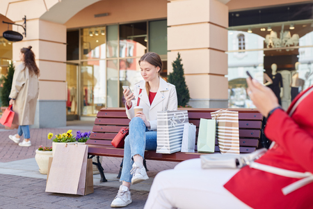 Girl sitting on bench with shopping bags Stock Photo