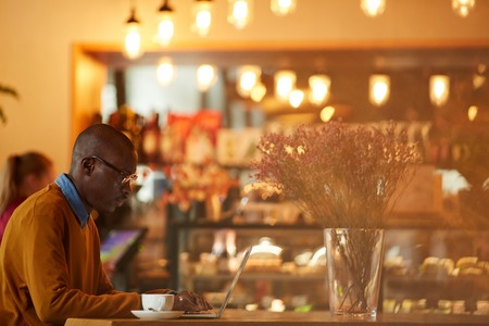 Contemporary African Man Working in Cafe