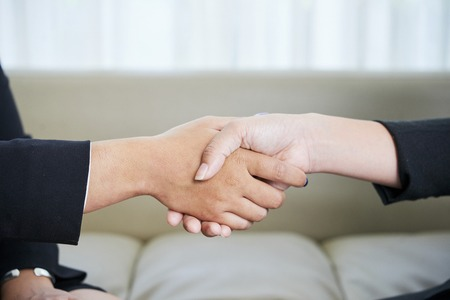 Close-up image of female business partners shaking hands to confirm deal Banco de Imagens