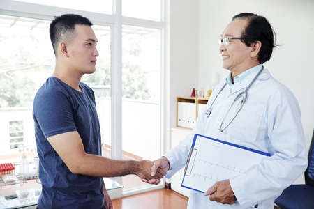 Smiling senior Asian doctor holding cardiogram and shaking hand of young patient