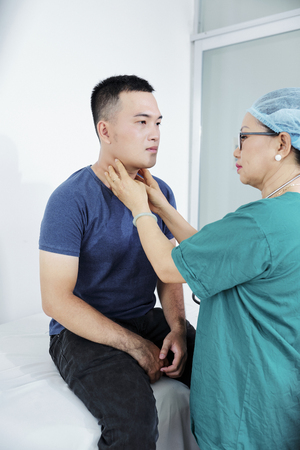 Female doctor in scrubs palpating neck of young man