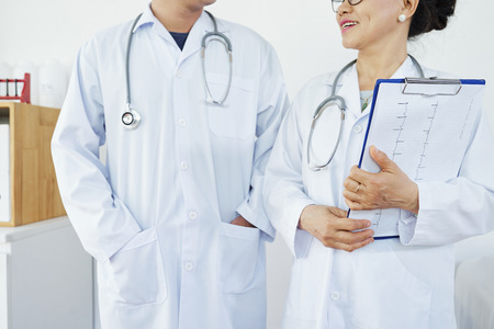 Cropped image of positive general practitioner with cardiogram talking to colleague