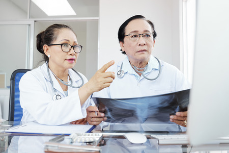 Serious concerned Vietnamese doctors holding lungs x-ray and reading results of its interpretation on computer screen