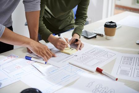 Manos de diseñadores de UX discutiendo documentos y trabajando en el diseño de estructura metálica del sitio web