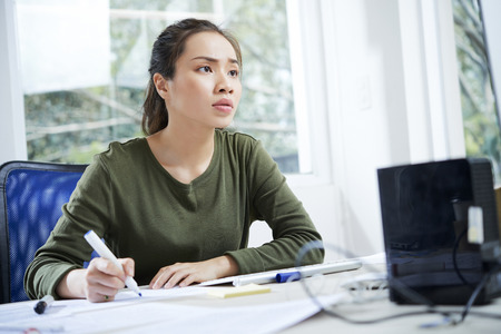Young Vietnamese UI designer working on website interface at her office table Imagens