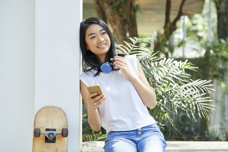 Portrait of pretty Vietnamese teenage girl with smartphone and headphones resting outdoors on summer day