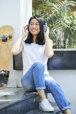 Positive Vietnamese teenage girl sitting on steps and listening to music in her headphones Stock Photo