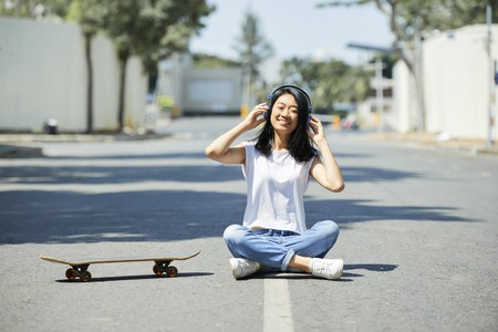 Pretty happy Asian teenage girl sitting on road next to skateboard and listening to music in her headphones