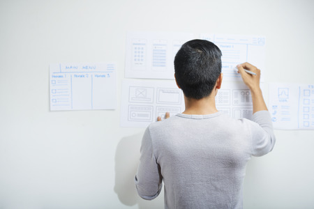Rear view of professional UI designer drawing wireframes for project on office wall