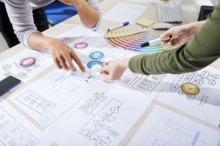 Diseñadores de UX que eligen íconos para aplicaciones móviles y discuten la estructura alámbrica