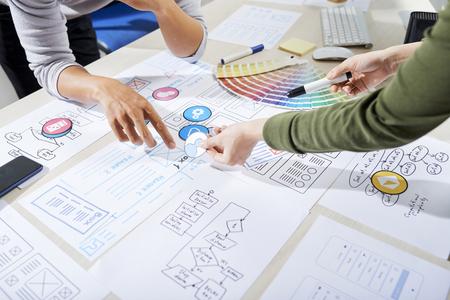 Projektanci UX wybierający ikony aplikacji mobilnej i omawiający model szkieletowy