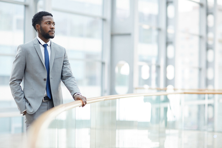 Pensive black businessman holding railing
