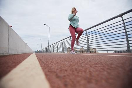 Jogging along bridge Фото со стока