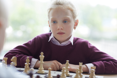 Blue-eyed girl playing chess Imagens - 124775781
