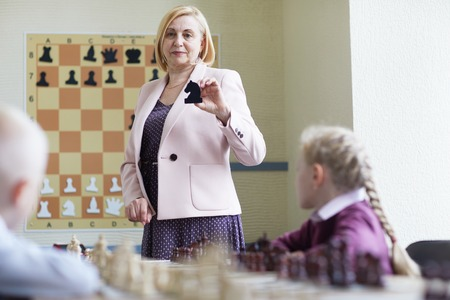 Teacher showing chess figures