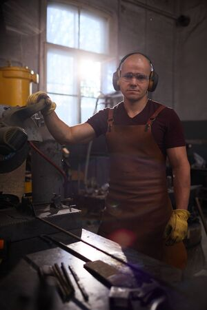 Young welder in smithy