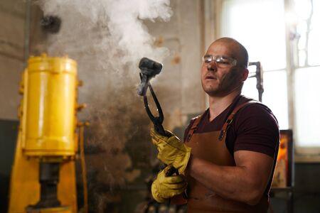 Forgeron chauve vérifiant la pièce en métal après trempe