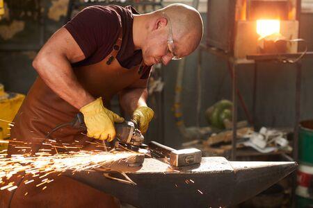 Jeune ouvrier polissant le métal avec le broyeur Banque d'images