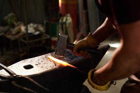 Blacksmith shaping heated metal bar Stock Photo