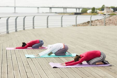 Side view portrait of three contemporary women doing yoga outdoors and stretching at dawn by river, copy space