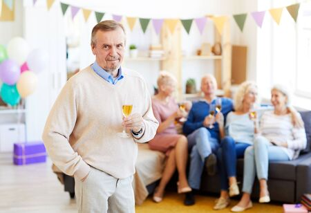 Portrait of content handsome elderly man with beard wearing casual sweater drinking champagne from flute at birthday party while his friends chatting in background