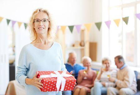 Positive lady holding big gift box