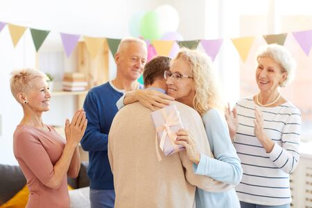 Lady hugging friend at birthday party Imagens
