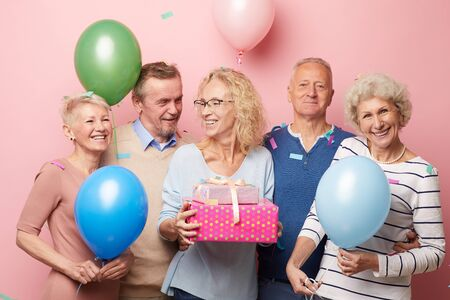 Excited friends congratulating mature lady with birthday Stok Fotoğraf