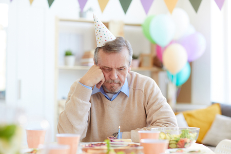 Lonely man looking at birthday cake with candle