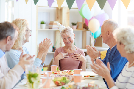 Friends clapping hands for birthday woman