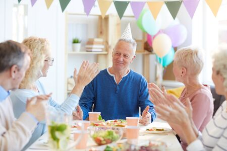 Applauding birthday man at dinner party