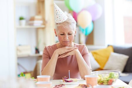 Pensive elderly woman celebrating birthday alone
