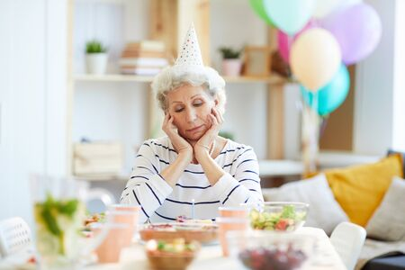 Unhappy retired lady having birthday party alone