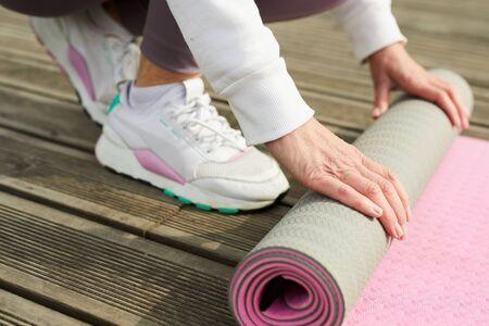 Sportive Woman Unrolling Mat
