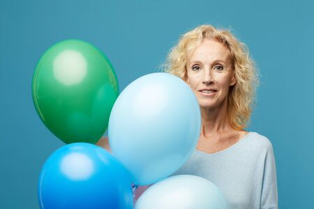 Beautiful lady with colorful helium balloons