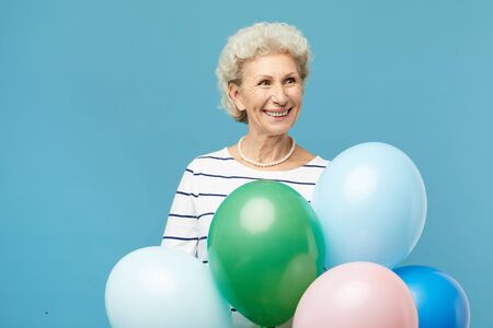 Happy elderly lady with bouquet of balloons