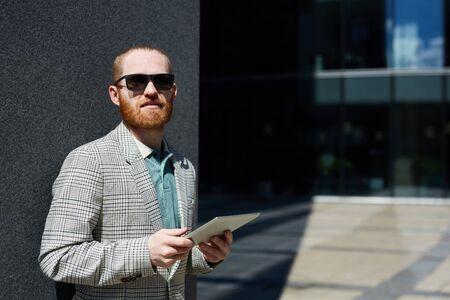 Confident hipster businessman using tablet