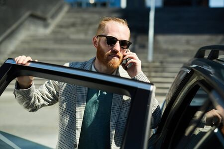 Confident businessman getting in cab Stock Photo